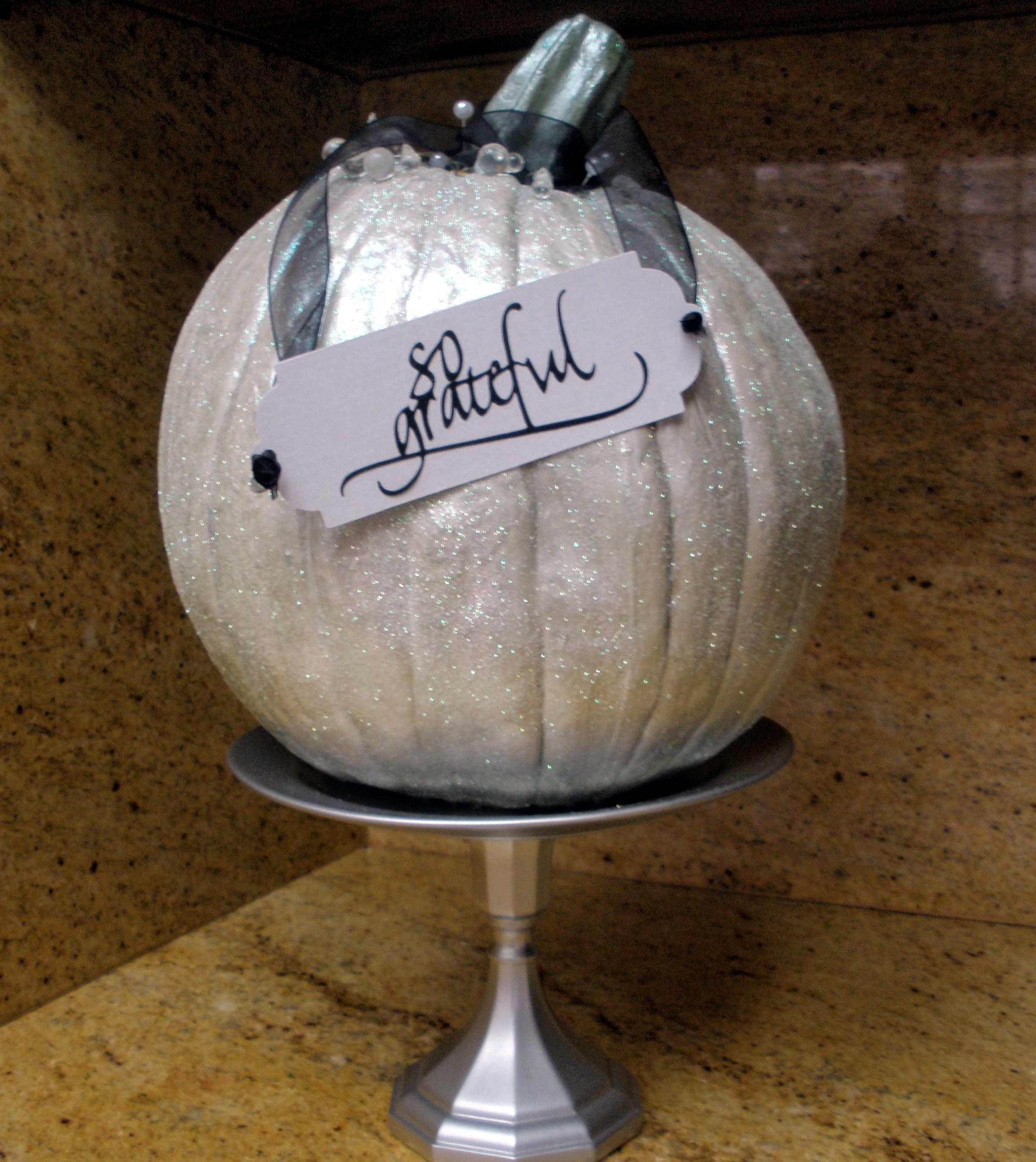 Glittered pumpkins on upcycled pedestal stands.